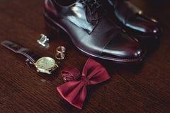 Sluit omhoog van moderne mensentoebehoren trouwringen, kers bowtie, leerschoenen, horloge en cufflinks Royalty-vrije Stock Afbeelding