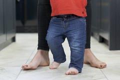 Sluit omhoog van Moeder die Babyzoon helpen om in Keuken te lopen royalty-vrije stock foto