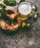 Sluit omhoog van mok van bier en pretzel met hop op donkere rustieke achtergrond, hoogste mening, exemplaarruimte stock foto's