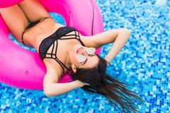 Sluit omhoog van mooi sexy meisje zwemmen op flamingo in pool in zonnebril De zomerroeping stock afbeelding
