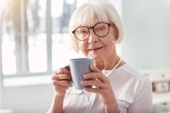 Sluit omhoog van mooie bejaarde het drinken koffie stock foto