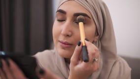 Sluit omhoog van moslimvrouw die make-up op haar gezicht die met borstel doen, oogschaduw toepassen Het moderne leven van moslimm stock footage