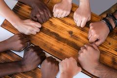 Sluit omhoog van multiraciale studentenhanden makend het gebaar van de vuistbuil stock foto