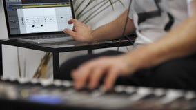 Sluit omhoog van musicus die het toetsenbord van Midi in de studio van de huismuziek spelen stock videobeelden