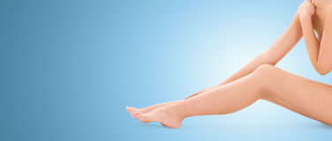 Sluit omhoog van naakte vrouwenbenen over blauwe achtergrond stock foto