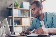 Sluit omhoog van nadenken jonge Afrikaanse knappe mens Hij draagt toevallige slim, zittend op het werk, kijkend in het laptop sch royalty-vrije stock afbeeldingen