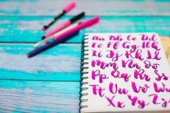 Sluit omhoog van notitieboekje met hand getrokken abc alfabetbrieven en kleurrijke pennen op blauwe houten bureauachtergrond stock afbeeldingen