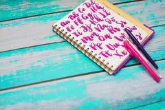 Sluit omhoog van notitieboekje met hand getrokken abc alfabetbrieven en kleurrijke pennen op blauwe houten bureauachtergrond royalty-vrije stock afbeelding
