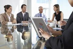 Sluit omhoog van Onderneemster Using Tablet Computer tijdens Raad Mee stock afbeeldingen