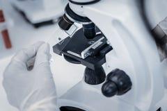 Sluit omhoog van onderzoeker die steekproef plaatsen onder microscoop stock foto's