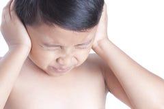 Sluit omhoog van ongelukkige jongen die aan lawaai lijden die zijn oren behandelen royalty-vrije stock fotografie