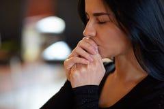 Sluit omhoog van ongelukkige vrouwen biddende god bij begrafenis stock afbeeldingen