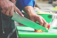 Sluit omhoog van onherkenbare kok scherpe uien en andere groenten met chef-kokmes terwijl het werken stock foto