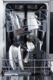Sluit omhoog van open afwasmachine met schone werktuigen in keuken Stock Foto