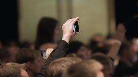 Sluit omhoog van opnamevideo met smartphone bij gebeurtenis voorraad De menselijke video van de handenspruit op de telefoon stock footage