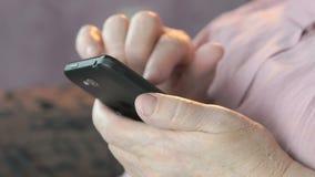 Sluit omhoog van oude gerimpelde handen houdend smartphone stock footage