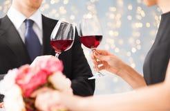Sluit omhoog van paar die rode wijnglazen clinking stock fotografie