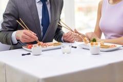 Sluit omhoog van paar die sushi eten bij restaurant Stock Afbeeldingen