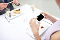 Sluit omhoog van paar met smartphones bij restaurant Royalty-vrije Stock Afbeelding