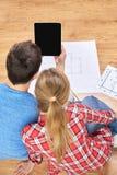 Sluit omhoog van paar met tabletpc en blauwdrukken Stock Foto