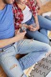 Sluit omhoog van paar met water het ontspannen in nieuw huis Stock Fotografie