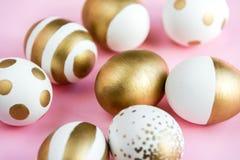 Sluit omhoog van paaseieren met gouden verf worden gekleurd die Diverse gestreepte en gestippelde ontwerpen Roze achtergrond Royalty-vrije Stock Foto's