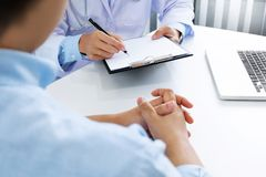 Sluit omhoog van patiënt en arts die nota's in het ziekenhuis of een kliniek nemen stock foto's