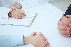 Sluit omhoog van patiënten handen en arts die nota's nemen Stock Afbeelding