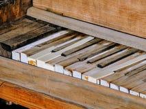 Sluit omhoog van pianosleutels van een rechte antiquiteit gebroken rustieke piano in openlucht in de woestijn van Arizona stock afbeeldingen