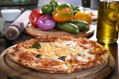 Sluit omhoog van pizza en ingrediënten Stock Afbeeldingen