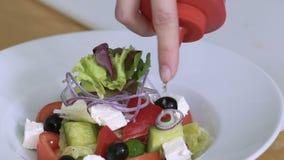Sluit omhoog van plantaardige salade gietende saus in kom Het gieten souce langzaam stock footage