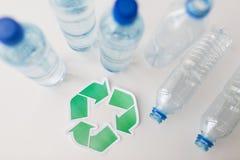 Sluit omhoog van plastic flessen en recyclingssymbool Royalty-vrije Stock Afbeeldingen