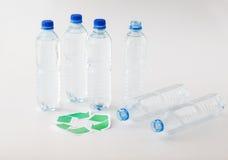 Sluit omhoog van plastic flessen en recyclingssymbool Stock Afbeeldingen