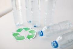 Sluit omhoog van plastic flessen en recyclingssymbool Stock Afbeelding