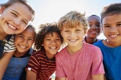 Sluit omhoog van pre-tienervrienden die in een park aan camera glimlachen stock afbeelding
