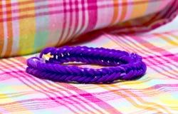 Sluit omhoog van purpere die kleurenarmbanden met elastiekjes worden gemaakt Stock Foto