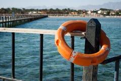 Sluit omhoog van Reddingsboei op pijler Oranje Reddingsboei voor veiligheid op water het leven bewaart materiaal voor noodsituati stock afbeeldingen