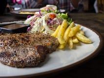 Sluit omhoog van Riblapje vlees met zout en peper, gouden frieten en groene groenten voor wit houten plaat, Vork en mes, Stock Afbeelding