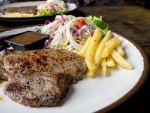 Sluit omhoog van Riblapje vlees met zout en peper, gouden frieten en groene groenten voor wit houten plaat, Vork en mes, Royalty-vrije Stock Foto's