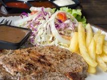 Sluit omhoog van Riblapje vlees met zout en peper, gouden frieten en groene groenten voor wit plaat, Vork en mes, houten Ta Royalty-vrije Stock Foto's