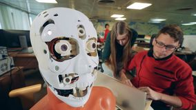 Sluit omhoog van robotachtig hoofd die zijn tong bewegen en aan technici die het controleren stock footage