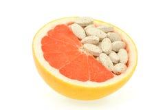 Sluit omhoog van rode geïsoleerde grapefruit en pillen Stock Afbeeldingen
