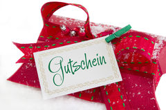 Sluit omhoog van rode huidige vakje en coupon met Duitse teksten voor chri royalty-vrije stock afbeelding