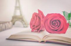 Sluit omhoog van rode roze bloemen bij geopend oud boek met uitstekende ton Stock Fotografie