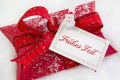 Sluit omhoog van rood huidig vakje met Duitse teksten voor Kerstmis - Coupon royalty-vrije stock afbeeldingen
