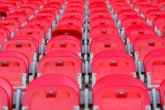 Sluit omhoog van rood opgevouwen zetels in voetbalstadion Stock Foto's