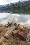Sluit omhoog van rotsen door meer Stock Afbeelding