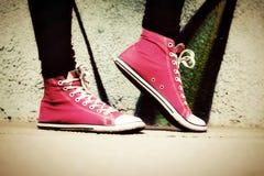 Sluit omhoog van roze tennisschoenen versleten door een tiener. stock foto