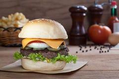 Sluit omhoog van rundvleeshamburger met kaas op houten lijst Royalty-vrije Stock Foto