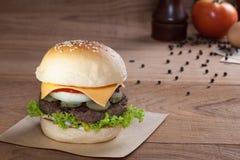 Sluit omhoog van rundvleeshamburger met kaas op houten lijst Royalty-vrije Stock Fotografie
